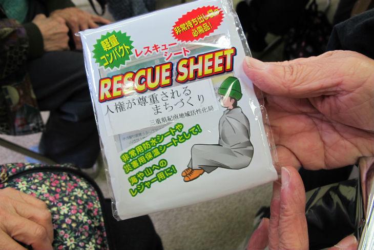 避難訓練で住民の一人が持参した、災害時に身体をおおい温めるレスキューシート